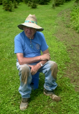 still gardening in 2004 with small Christmas trees growing in background and wearing a goofy hat my mom bought for him at a garage sale to protect him from the sun